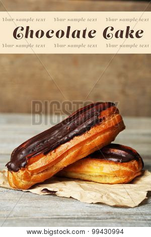 Tasty eclairs on wooden table, close up