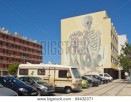 Large artwork of Skeleton painted on side of apartment block.