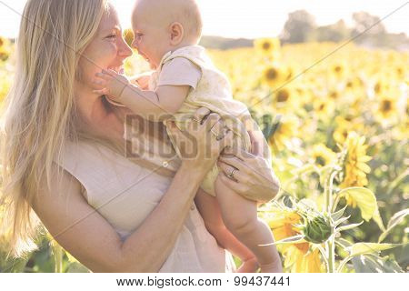 Happy Mother And Baby Daughter In Sunflower Field