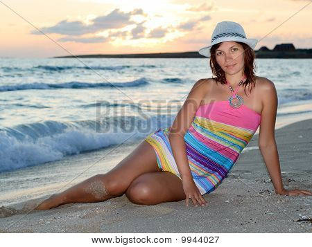 Woman In A Colorful Dress And Hat On The Beach