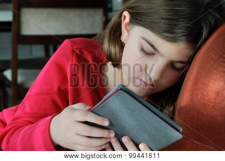 Girl Reading Book On E-reader