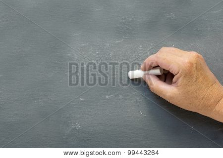 Older Hand Writes On A Blank Chalkboard