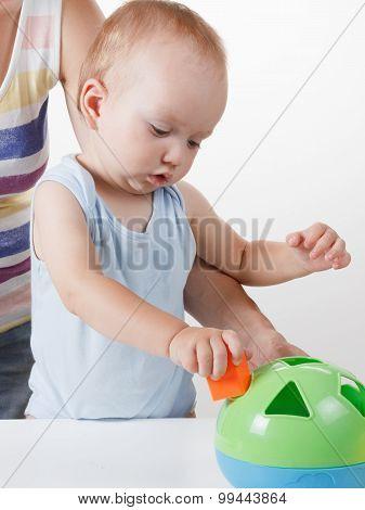 Mom teaches the baby to put toys. Studio shoot