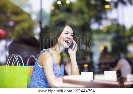 Smiling Young Woman Talking On The Phone In Cafe Shop