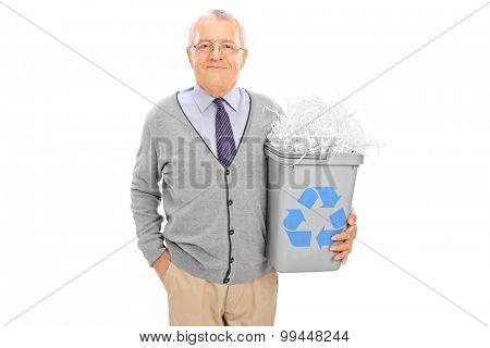Cheerful senior holding a recycle bin full of shredded paper and looking at the camera isolated on white background