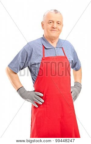 Vertical shot of a mature man in a red apron and gray gloves looking at the camera isolated on white background