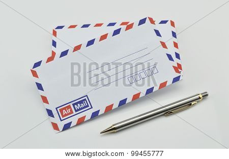 Stack Of Air Mail Envelopes And Pen On White