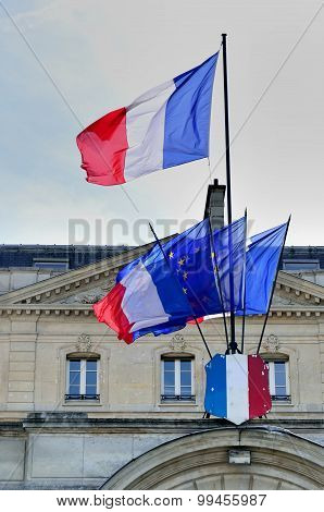 group of French flags in front of building