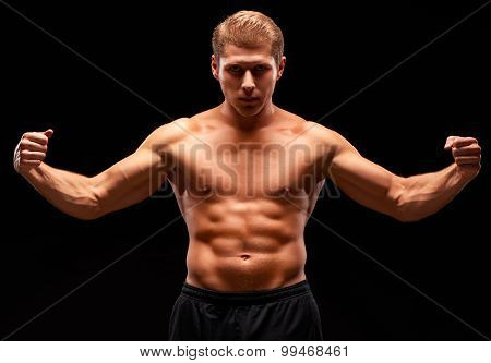 Muscular heavy sexy man in tense pose with raised arms and tense muscles
