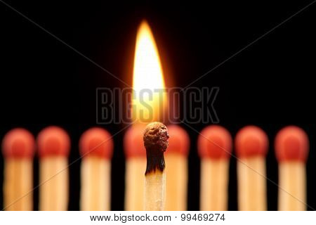 Burning match standing in front of eight red wooden matches