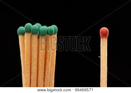 Group of green wooden matches standing with red match isolated on black