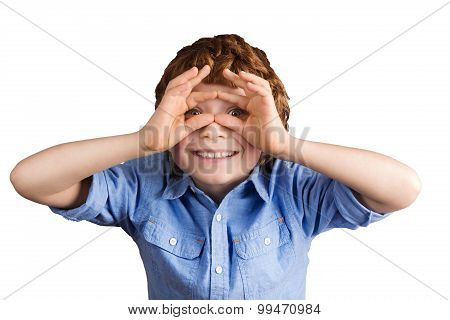 Handsome smiling boy makes aviator glasses with his hands. Isolated on white background