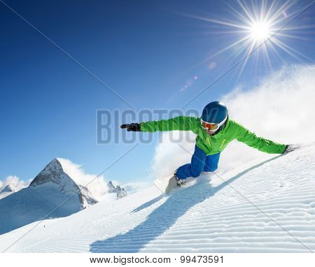 Snowboarder skiing in high mountains.