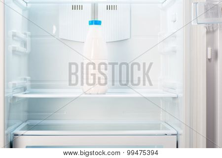 Bottle of yoghurt on shelf of open empty refrigerator