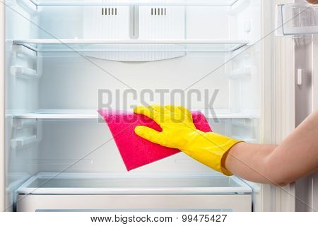 Woman's hand in yellow glove cleaning refrigerator with pink rag
