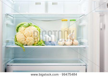 Cauliflower white eggs champignon mushrooms and two glass bottles of yoghurt on shelf of open empty