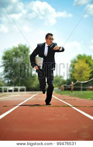 Businessman Looking Wrist Watch Watch Running On Athletic Track In Stress