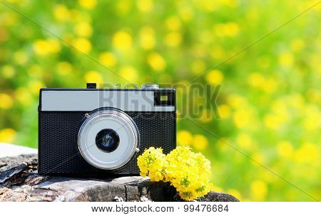 Retro Vintage Camera With Yellow Flowers Over Sunny Summer Bokeh Background