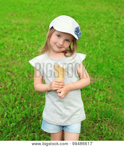 Portrait Of Little Girl Child In Cap With Ice Cream On The Grass In Summer Day
