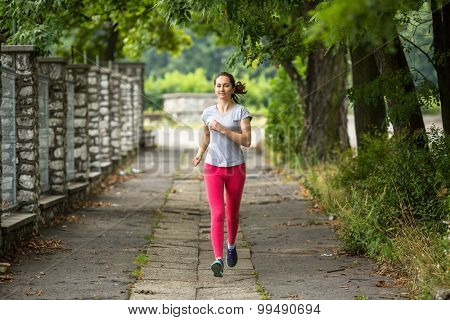 Young woman running on the track through the summer park. Training outdoors. Workout in a Park.