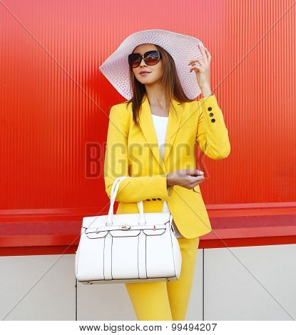 Fashion Elegant Woman Wearing A Yellow Suit Clothes, Straw Hat, Sunglasses And Handbag Over Colorful