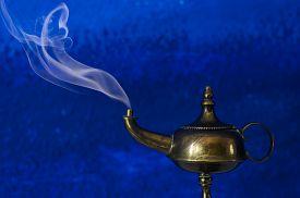stock photo of aladdin  - Aladdin lamp make a wish concept smoke and blue background - JPG