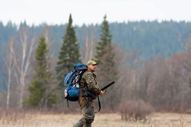 picture of hunter  - The hunter with rucksack and gun on the field - JPG