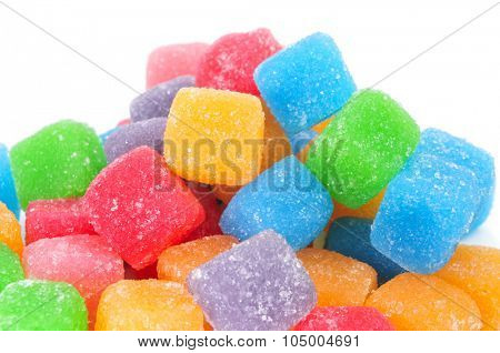 closeup of some cubic gumdrops of different colors on a white background