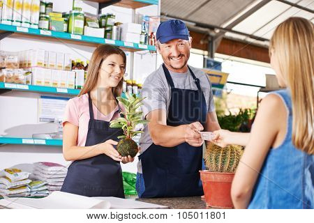 Woman paying plant in nursery shop of a garden center