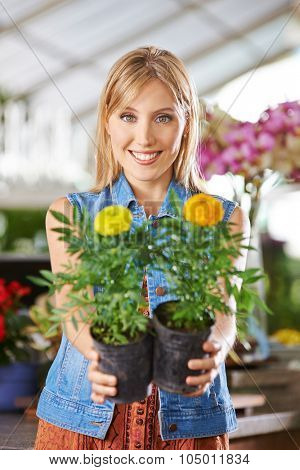 Smiling gardener in nursery with two yellow flowers (tagetes) in her hands