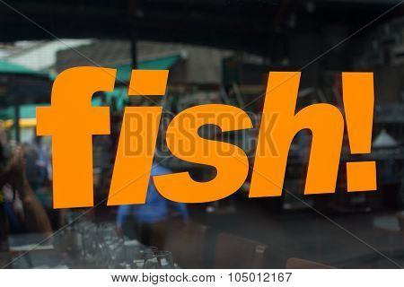 Window Sign With The Word Fish In Bright Orange Letters