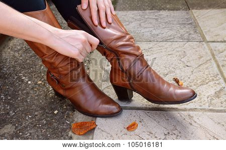 Woman Zipping Up High-heeled Tan Leather Boots