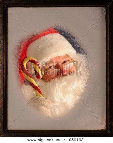 Papai Noel na janela com o bastão de doces