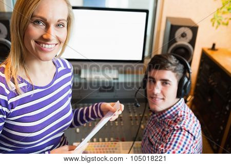 Portrait of female employee with male radio host against sound mixer and monitor in studio
