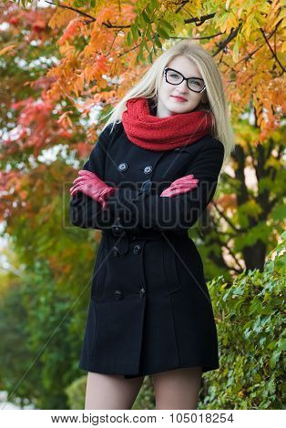 Attractive student girl with crossed arms wearing cat eye glasses posing at red autumn foliage backg