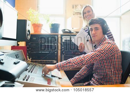 Portrait of male radio host using sound mixer while female employee standing in studio