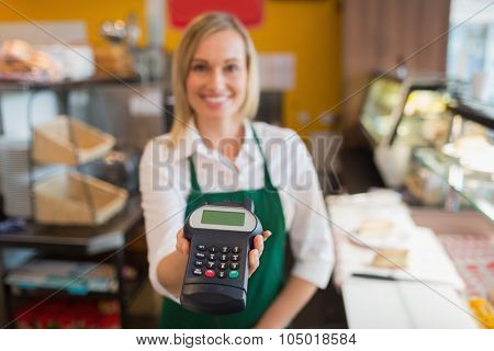 Portrait of female shop owner holding credit card reader in bakery