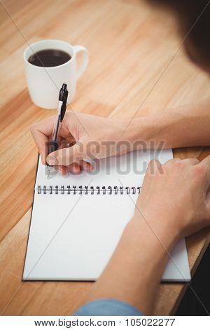 Cropped hand of hipster writing on spiral notebook at desk in office