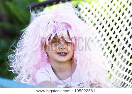 Portrait Of A Little Girl In The Carnival Wig Of Hair Color In The Sun.