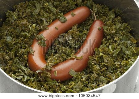 Cooking pot with cooked curlly kale and smoked sausage