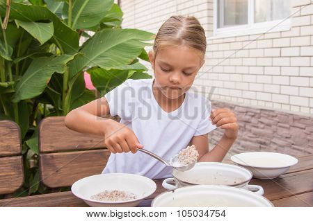 Girl With A Ladle Of Porridge Shifts The Pan In A Bowl