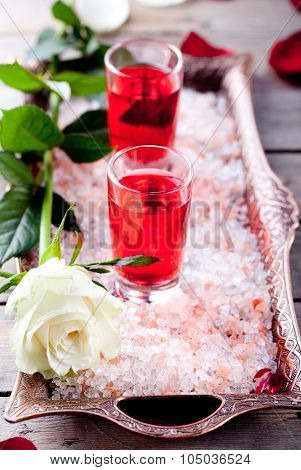 Rose flavor liqueur in shot glasses on pink salt