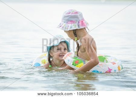 Two Girls Are Swimming In The River