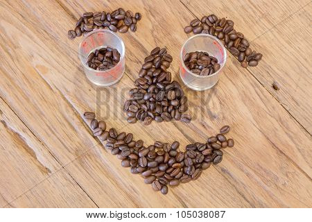 Coffee Beans In Smile Face Shape On Wood Table
