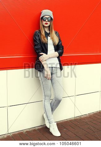 Fashion Stylish Pretty Woman Wearing A Rock Black Leather Jacket And Sunglasses With Hat Over Red Ba