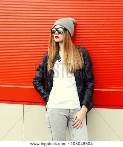 Fashion Stylish Woman Wearing A Rock Black Leather Jacket And Sunglasses With Hat Over Red Backgroun