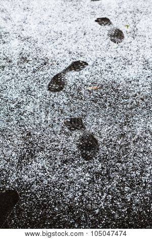 Human Footprints On Sidewalk Covered By First Snow