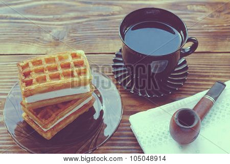 Cup Of Tea, Viennese Waffles And Tobacco Pipe On Wood Table