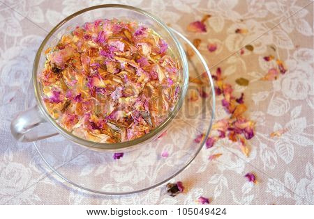 Gentle composition of the drink of tea rose petals, transparent cup and saucer and scattered petals