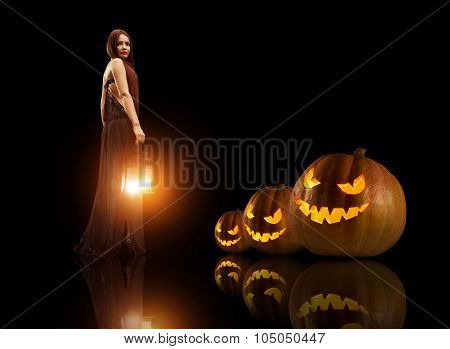 Beautiful Witch With The Magic Lantern. Halloween Pumpkins On The Background.